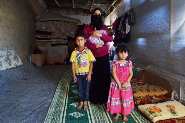 Ratiba Awad with her three children, Ouday (5), Ahraa (4) and Batoula (7 months), in the abandoned cow shed where they live with over 20 other Syrian refugees since having to flee their homes due to the war in Syria (Photo: Eoghan Rice / Trócaire)
